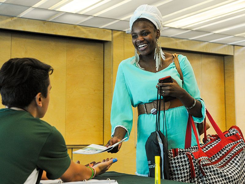 A student accepts a brochure at an orientation session